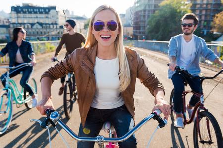 adentro y afuera: Solo una amistad y carretera. Hermosa joven sonriente mujer en bicicleta a caballo y mirando a la cámara mientras sus amigos a caballo en el fondo Foto de archivo