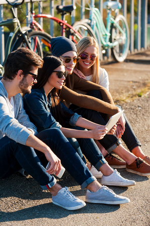 young group: Young and carefree. Close-up of group of young smiling people bonding to each other and looking at digital tablet while sitting outdoors together with bicycles in the background Stock Photo