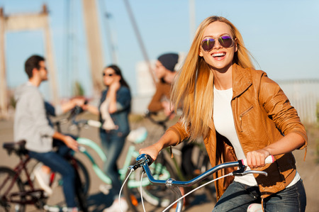 carefree: Are you ready to have some fun? Beautiful young smiling woman leaning at her bicycle and looking at camera while her friends talking in the background Stock Photo