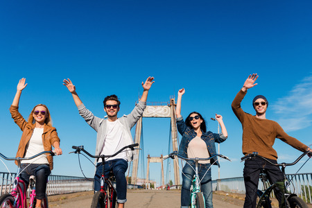 recreational: Enjoying fun ride. Low angle view of four young cheerful people riding their bicycles and keeping arms raised Stock Photo