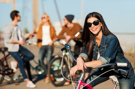carefree: Ready to fun and adventures. Beautiful young smiling woman leaning at her bicycle and looking at camera while her friends talking in the background Stock Photo