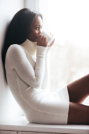 nude woman sitting: Enjoying fresh and hot coffee. Thoughtful young African woman in warm sweater looking through a window while sitting on the window sill and drinking coffee