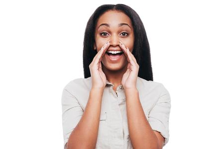 mujer alegre: Al anunciar una buena noticia. Alegre joven mujer africana de la mano alrededor de la boca y gritando mientras está de pie contra el fondo blanco