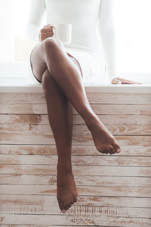 nude woman sitting: Maybe coffee break? Cropped image of gorgeous young African woman with beautiful legs sitting on the window sill and holding coffee cup