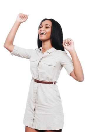 puños cerrados: Belleza exitosa. Mujer que guarda jóvenes africanos Brazos felices levantadas y los ojos cerrados mientras está de pie contra el fondo blanco Foto de archivo
