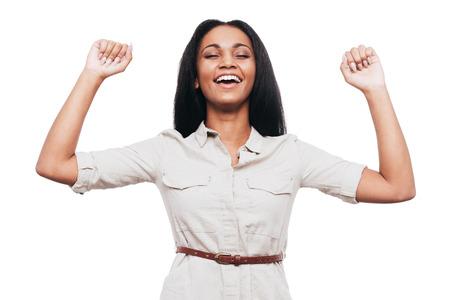 puños cerrados: Joven y exitoso. Mujer que guarda jóvenes africanos Brazos felices levantadas y los ojos cerrados mientras está de pie contra el fondo blanco