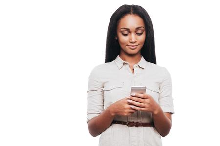 mujer bonita: Escribiendo mensaje a un amigo. Mujer africana joven confidente que sostiene el tel�fono m�vil y mirarlo mientras est� de pie contra el fondo blanco