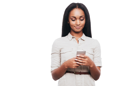 african ethnicity: Typing message to friend. Confident young African woman holding mobile phone and looking at it while standing against white background