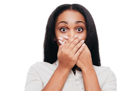Unbelievable news! Shocked young African woman covering mouth with hands and looking at camera while standing against white background Stock Photo