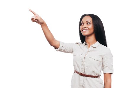 woman pointing: Look at that! Beautiful young African woman pointing away and smiling while standing against white background