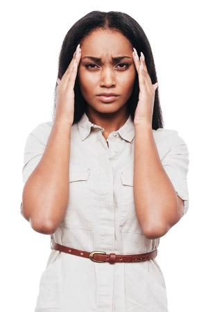 dolor de cabeza: Que sufren de dolor de cabeza. Mujer africana joven frustrada toc�ndose la cabeza con las manos y mirando a la c�mara mientras est� de pie contra el fondo blanco
