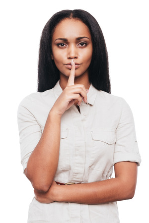 ? ?  ? �silence: �Guardar silencio! Mujer africana joven confidente que sostiene el dedo en los labios mientras est� de pie contra el fondo blanco Foto de archivo