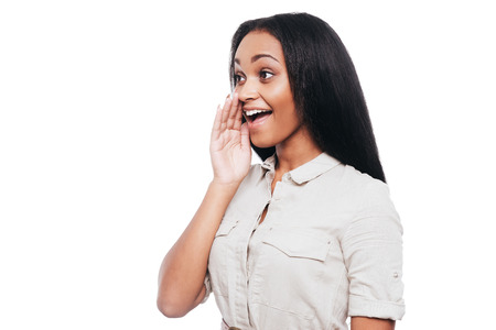 mujer alegre: Compartiendo buenas noticias. Vista lateral de la joven alegre mujer africana de la mano alrededor de la boca y gritando mientras está de pie contra el fondo blanco Foto de archivo