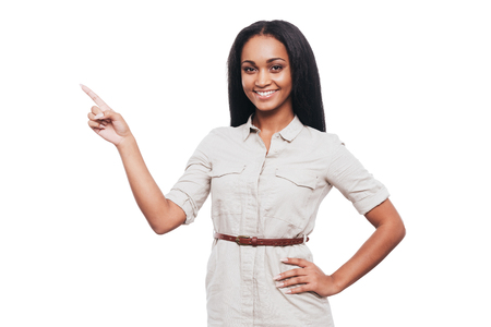 woman pointing: Pointing copy space. Smiling young African woman holding hand on hip and pointing away while standing against white background