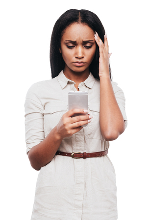 woman only: Bad news. Frustrated young African woman holding mobile phone and looking at it while standing against white background
