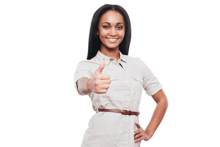 mujer alegre: Los pulgares para arriba para el éxito! la joven mantener su pulgar para arriba una sonrisa mientras está de pie contra el fondo blanco sonriente Foto de archivo