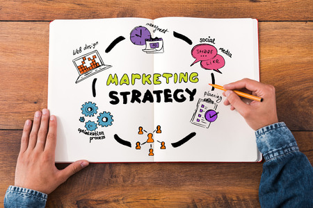 Marketing Strategy: Marketing strategy. Top view close-up image of man holding hands on his notebook with colorful sketches while sitting at the wooden desk