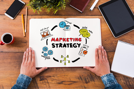 success strategy: Planning marketing strategy. Top view close-up image of man holding hands on his notebook with colorful sketches while sitting at the wooden desk