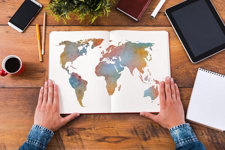 путешествие: Планирование свою поездку. Вид сверху крупным планом изображение человека, держащего руки на своем ноутбуке с картой красочный на нем в то время, сидя на деревянный стол