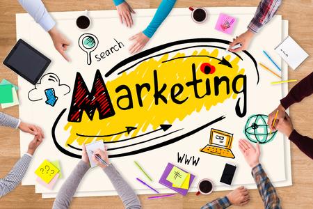 bocetos de personas: Discusión de la estrategia de marketing. Vista superior de papel con dibujos de colores que ponen en la mesa de madera y la gente sentada alrededor de él Foto de archivo
