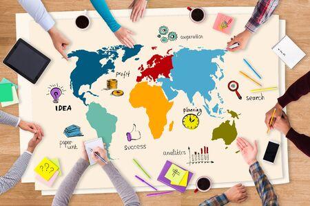 bocetos de personas: Discutir nuevas oportunidades. Vista superior de papel con dibujos de colores que ponen en la mesa de madera y la gente sentada alrededor de él Foto de archivo