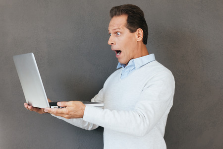 mouth  open: What is that? Surprised mature man looking at laptop and keeping mouth open while standing against grey background Stock Photo
