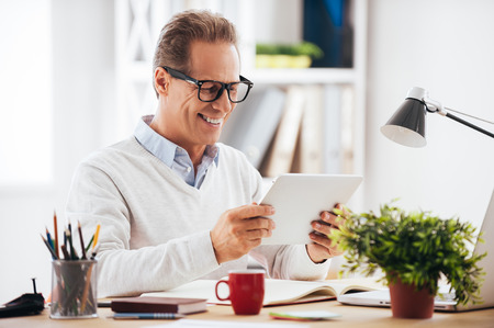 fifties: Technologies making life easier. Cheerful mature man holding digital tablet and looking at it with smile while sitting at his working place