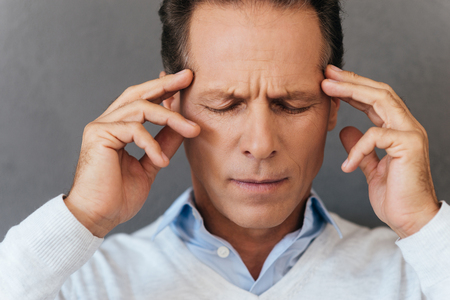 awful: Feeling awful headache. Frustrated mature man touching his head with fingers and keeping eyes closed while standing against grey background Stock Photo