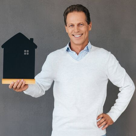 real business: Happy house owner. Confident mature man holding house shaped object in hand and smiling while standing against grey background Stock Photo