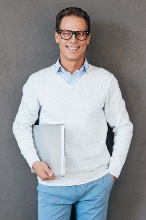 Confident IT expert. Confident mature man carrying laptop and looking at camera with smile while standing against grey background