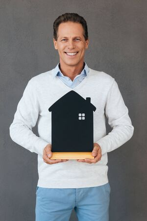 only one senior adult man: Ready to move in. Confident mature man holding house shaped object in hand and smiling while standing against grey background