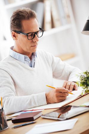 hombre escribiendo: Concentrado en el trabajo. Hombre maduro confidente escribiendo algo en su cuaderno mientras estaba sentado en su lugar de trabajo