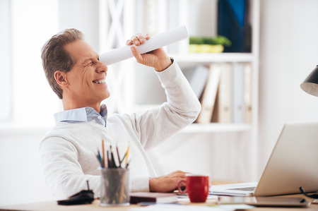 break from work: Looking for new opportunities. Playful mature man holding handmade paper telescope and looking through it with smile while sitting at his working place