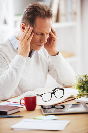work stress: Feeling headache. Frustrated mature man touching his head and keeping eyes closed while sitting at his working place Stock Photo