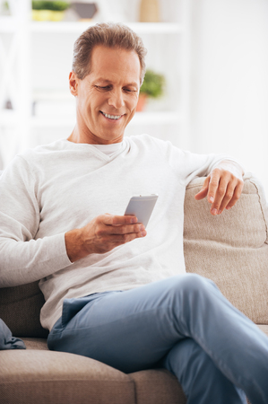 text message: Texting to friend. Confident mature man holding mobile phone and looking at it with smile while sitting on the couch at home Stock Photo