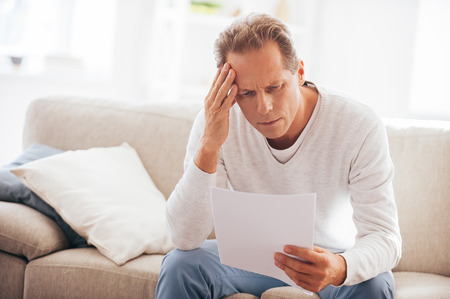 document: Bad news. Depressed mature man holding paper and looking at it while sitting on the couch at home Stock Photo