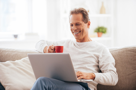 surfing the net: Surfing net at home. Cheerful mature man working on laptop and drinking coffee while sitting on the couch at home