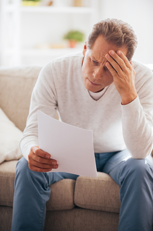 financial problems: Financial problems. Frustrated mature man holding paper and looking at it while sitting on the couch at home