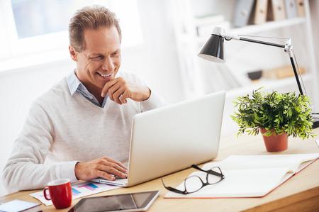 Tevreden met zijn werk. Vrolijke volwassen man werken op laptop en glimlachen tijdens de vergadering op zijn werkplek