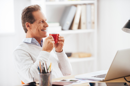 mature man: Starting his working day with coffee. Cheerful mature man holding coffee cup and looking away while sitting at his working place Stock Photo