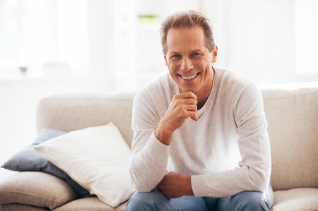 그는 솔직한 미소를 얻었다. 집에서 소파에 앉아있는 동안 명랑 성숙한 지주 턱에 손을 카메라를 찾고 스톡 콘텐츠