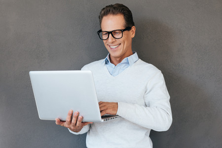smiling businessman: IT support. Confident mature man working on laptop and smiling while standing against grey background