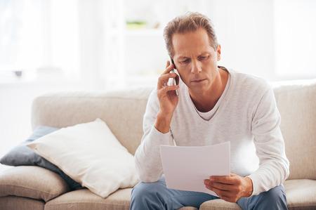 factura: Hablar de ese documento. Hombre maduro serio que sostiene el papel y hablando por el teléfono móvil mientras se está sentado en el sofá en casa
