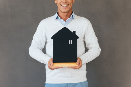 mature man: New house owner. Cropped image of mature man holding house shaped object in hand and smiling while standing against grey background Stock Photo