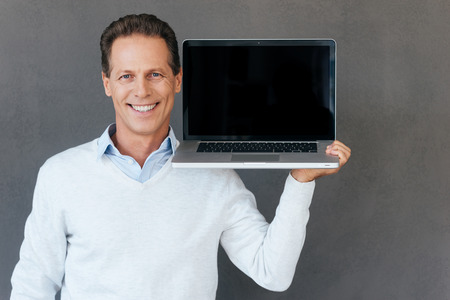 shoulder carrying: Copy space on his laptop. Confident mature man  carrying laptop on shoulder and smiling while standing against grey background