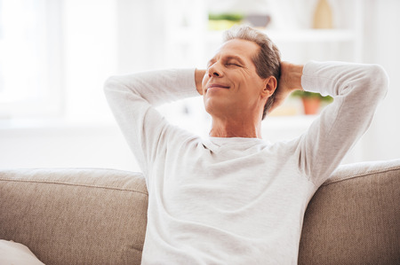 hands on head: Enjoying free time at home. Cheerful mature man holding hands behind head and looking relaxed while sitting on the couch at home