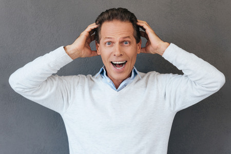 expressing positivity: That is unbelievable! Surprised mature man touching head with hands and expressing positivity while standing against grey background Stock Photo