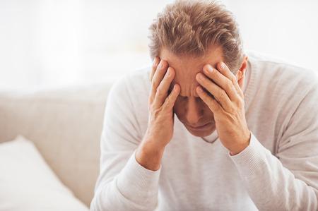 depresi�n: Sentirse cansado y deprimido. Hombre maduro deprimido que cubre la cara con las manos mientras est� sentado en el sof� en casa