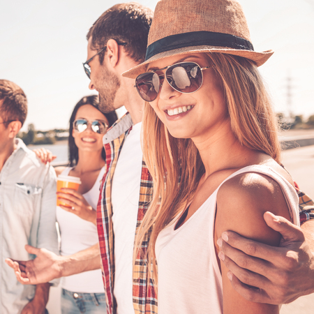 young group: Enjoying time with friends. Group of young happy people talking to each other while beautiful woman looking at camera and smiling