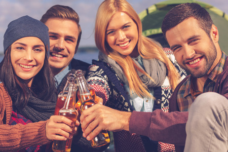 near beer: Cheers to friends! Four young happy people cheering with beer and smiling while sitting near the tent together